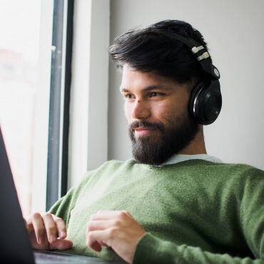 Man is smiling as he uses confidential and secure online counseling services from the comfort of his home office.