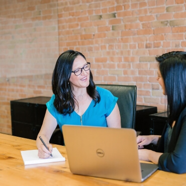 Two business women sit at a desk in a corporate office in Cincinnati and discuss effective workplace solutions and ways to prevent employee burnout.
